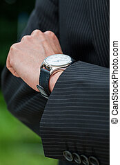 Man in suit checking the time