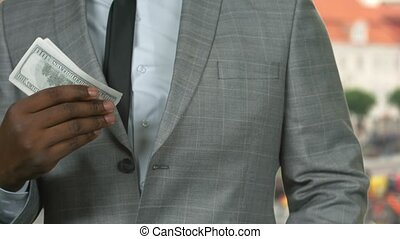 Man in suit counting money.