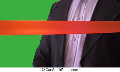 Man in suit cutting red ribbon
