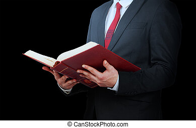Man in suit holding a opened book on a black background