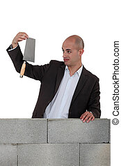 Man in suit holding a trowel behind a brick wall