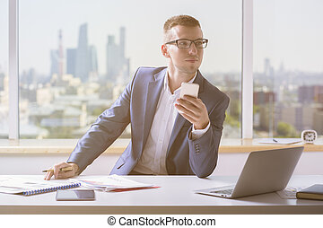 Man in suit holding cellphone