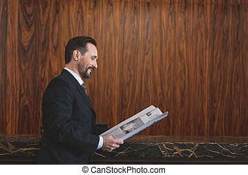 Man in suit holding journal near reception desk