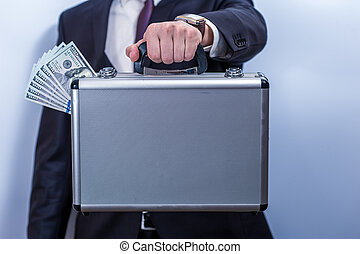 Man in suit holds metal briefcase with dollars