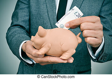 man in suit introducing a pound sterling bill in a piggy...