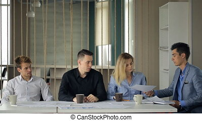 Man in suit jacket give through chain, documents woman and other people sitting at same table.