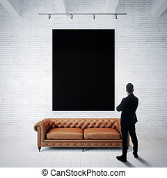 Man in suit looking at black poster holding on the white brick wall. Classic sofa, wood floor. Vertical