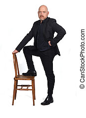 man in suit playing with a chair on white background