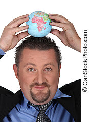 Man in suit putting a globe on his head