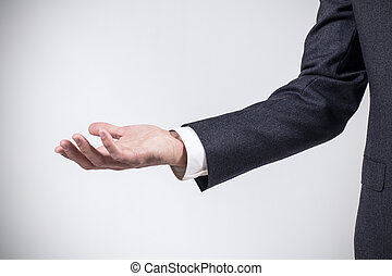 Man in suit shows outstretched hand with open palm.