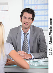 Man in suit sitting across a desk from a young woman with a schedule in the background