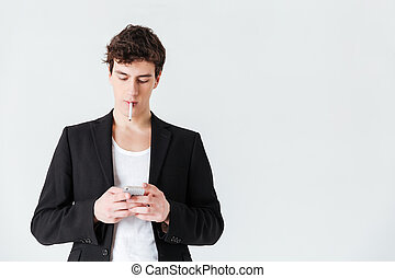 Man in suit smoking cigarette and using smartphone