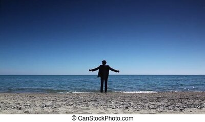 Man in suit stand on beach