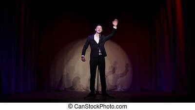 Man in suit stand up comedian speaking jokes in micropphone standing on stage. Funny performance. Comedian clapping hands overhead and calling audience doing the same.