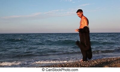 Man in suit standing on beach and putting of jacket