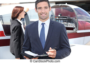 Man in suit taking notes in front of an airplane