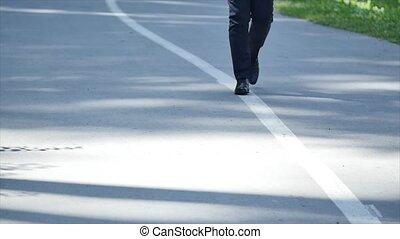 Man in suit walking on the road slowmo