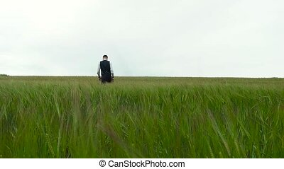 man in suit walking through the green field