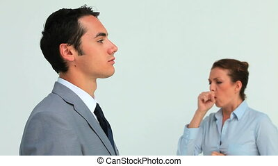 Man in suit wearing a surgical mask while a woman is sneezing