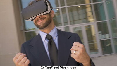Man in suit wearing VR goggles celebrating victory while camera circles him