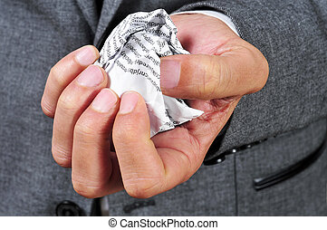 man in suit with a crumpled piece of paper
