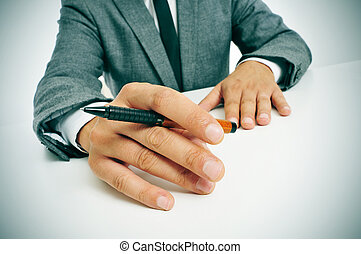 man in suit with a pen in his hand