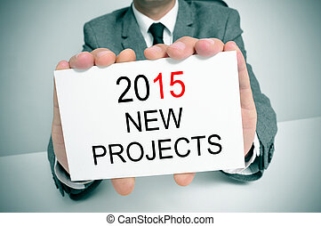 man in suit with a signboard with the text 2015 new projects