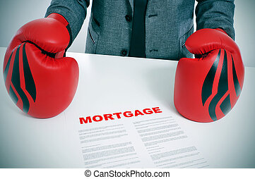 man in suit with boxing gloves and a mortgage contract