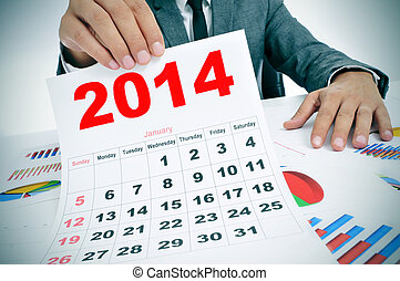 man in suit with charts and a 2014 calendar - man wearing a...