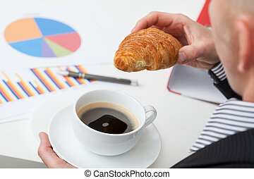 Man in suit with coffee and roll