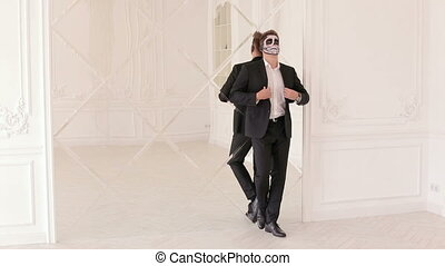 Man in suit with Halloween skull make-up, he stands leaning on the mirror wall.