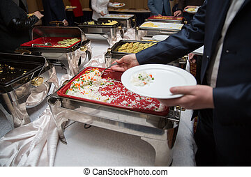 man in suits choosing food at a banquet