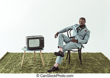 man in sunglasses and suit on chair with tv
