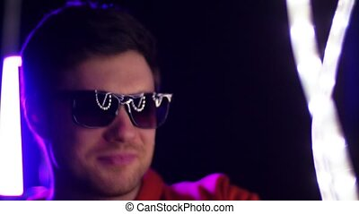 man in sunglasses dancing over neon lights - leisure,...
