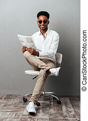 Man in sunglasses holding newspaper while sitting in a chair