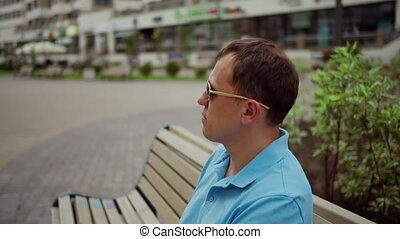 Man in sunglasses is resting while sitting on a bench on a blurred background of the city