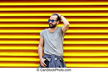 man in sunglasses over ribbed yellow background - fashion,...