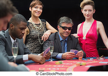 Man in sunglasses playing poker with two women either side