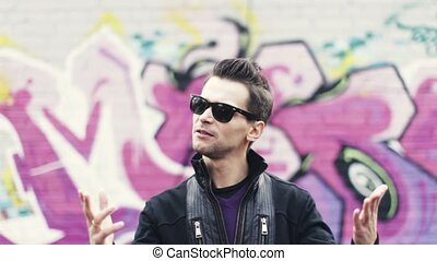 Man in sunglasses, sway gesture, sing in camera. Artist. Graffiti wall on background. Subculture