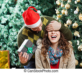 Man In Surprising Woman With Christmas Gift At Store - Young...
