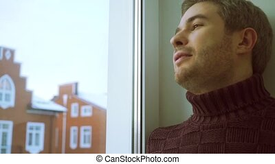 Man in sweater coming up to the window, looking through it and smiling