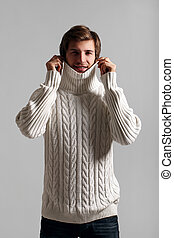 Man in sweater protecting his neck from cold