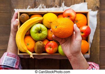 Man in tartan plaid shirt holds a box full of fresh fruits and a big juicy orange. Fruit harvest - apples, oranges, lemon, kiwi, banana. Rustic wooden table.