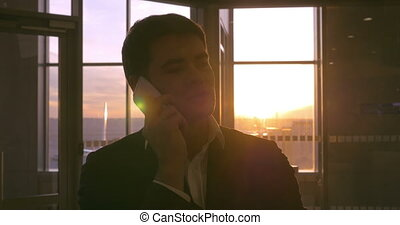 Man in the airport having a phone talk at sunset