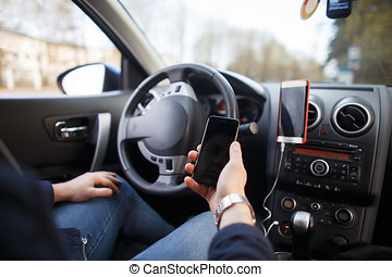 Man in the car is holding a mobile phone