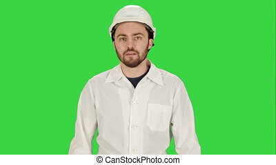 Man in the construction helmet with a raised finger on a Green Screen, Chroma Key.