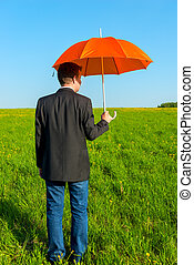 man in the field with orange umbrella
