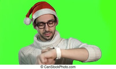 Man in the hat of Santa Claus using smartwatch touchscreen, cute smiles on a green background