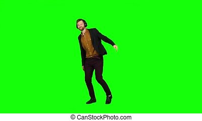 Man in the headphones bounces on the spot and raises his hands up. Green screen