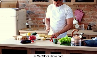 man in the kitchen cuts a baguette - attractive man in the...